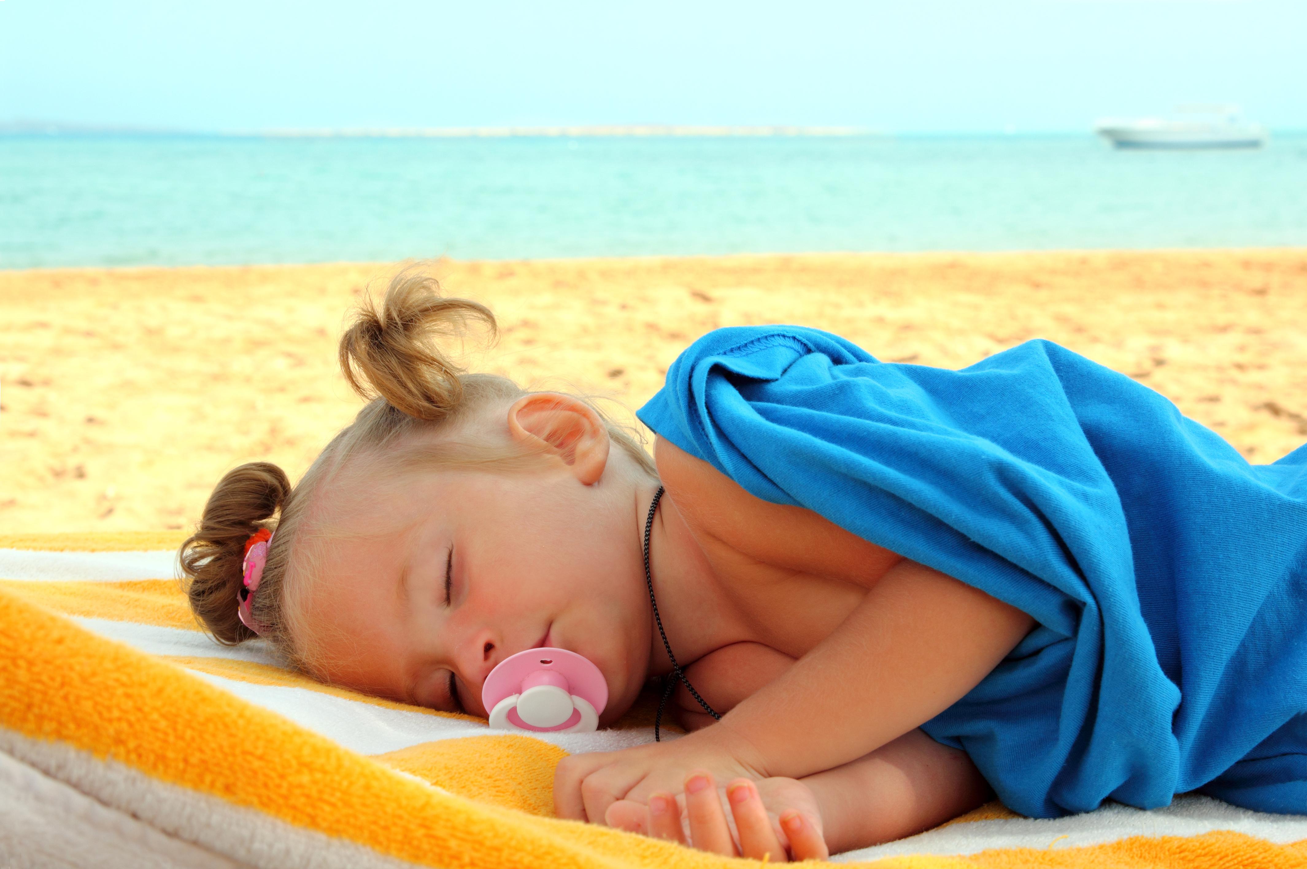 little girl sleeping on beach
